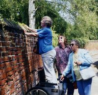 Former land girl Irene Grimwood looking over the wall at the Halesworth rectory